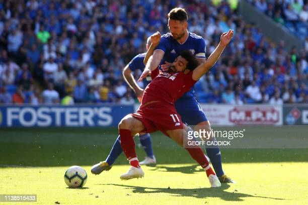 TOPSHOT Liverpool's Egyptian midfielder Mohamed Salah is fouled by Cardiff City's English defender Sean Morrison to earn a penalty leading their...