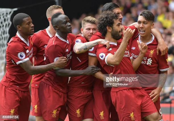 TOPSHOT Liverpool's Egyptian midfielder Mohamed Salah is mobbed by teammates as he celebrates scoring his team's third goal during the English...
