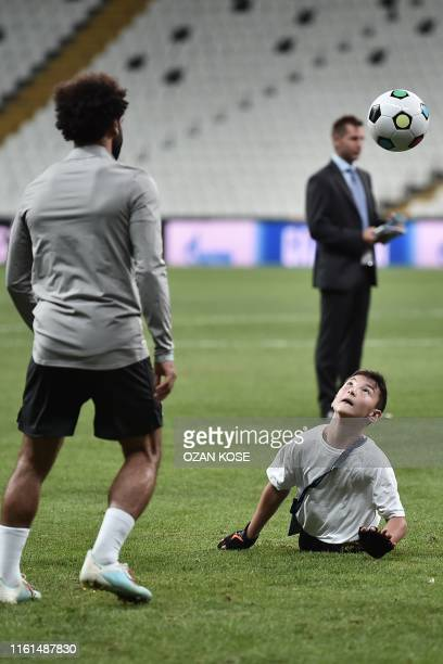 Liverpool's Egyptian midfielder Mohamed Salah plays football with a child at the end of a training session ahead of the UEFA Super Cup 2019 football...