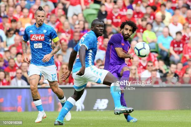 Liverpool's Egyptian midfielder Mohamed Salah plays the ball past Napoli's Senegalese defender Kalidou Koulibaly and Napoli's Slovakian midfielder...