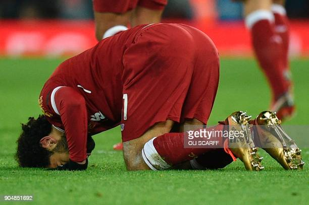 Liverpool's Egyptian midfielder Mohamed Salah puts his head on the pitch after scoring their fourth goal to make the score 41 during the English...