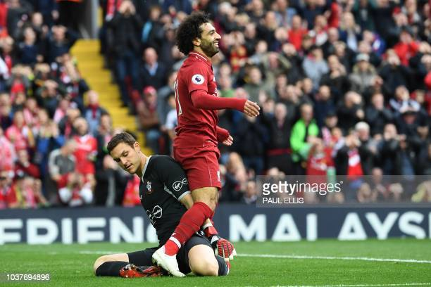 Liverpool's Egyptian midfielder Mohamed Salah reacts with Southampton's English goalkeeper Alex McCarthy to a missed chance at goal during the...