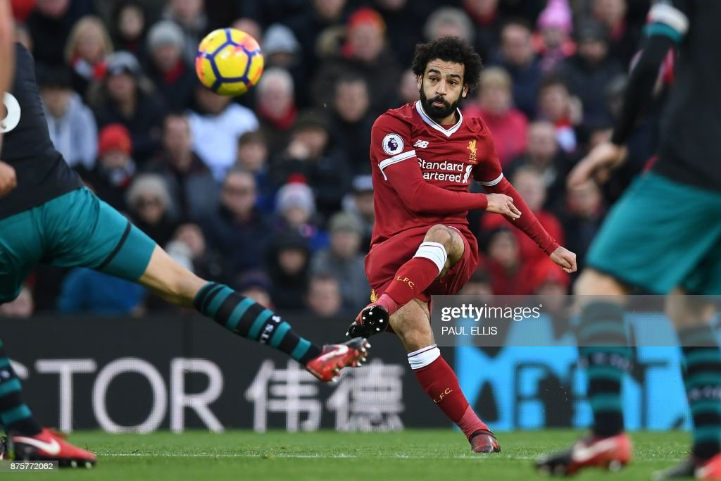 Liverpool's Egyptian midfielder Mohamed Salah scores the opening goal during the English Premier League football match between Liverpool and Southampton at Anfield in Liverpool, north west England on November 18, 2017. / AFP PHOTO / Paul ELLIS / RESTRICTED TO EDITORIAL USE. No use with unauthorized audio, video, data, fixture lists, club/league logos or 'live' services. Online in-match use limited to 75 images, no video emulation. No use in betting, games or single club/league/player publications. /