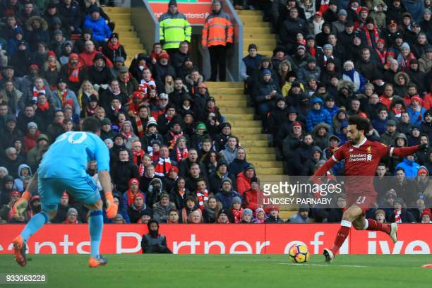 Liverpool's Egyptian midfielder Mohamed Salah scores the team's first goal during the English Premier League football match between Liverpool and...