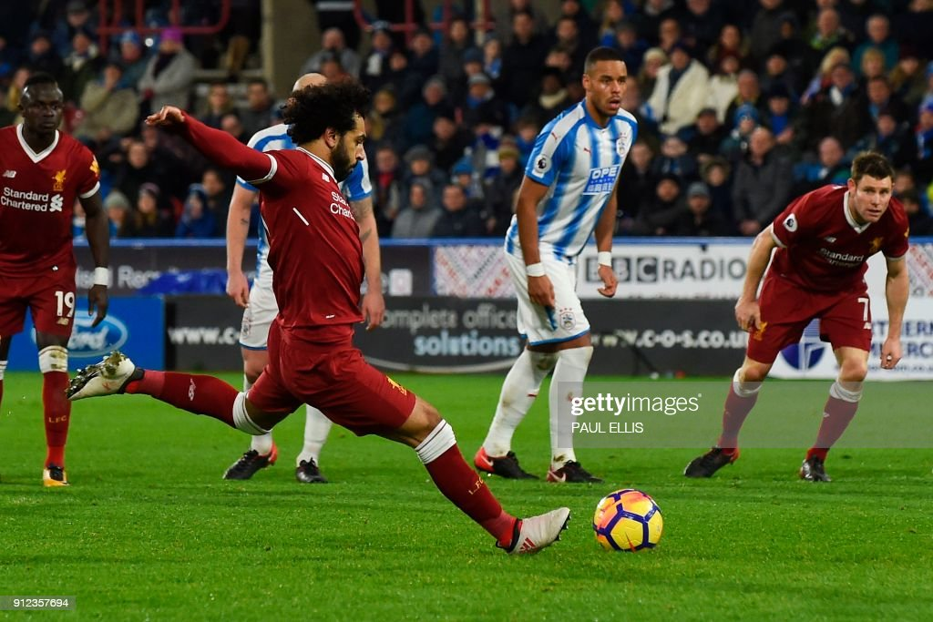 Liverpool's Egyptian midfielder Mohamed Salah scores their third goal from the penalty spot during the English Premier League football match between Huddersfield Town and Liverpool at the John Smith's stadium in Huddersfield, northern England on January 30, 2018. / AFP PHOTO / PAUL ELLIS / RESTRICTED TO EDITORIAL USE. No use with unauthorized audio, video, data, fixture lists, club/league logos or 'live' services. Online in-match use limited to 75 images, no video emulation. No use in betting, games or single club/league/player publications. /
