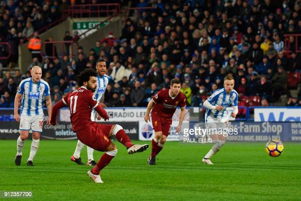 Liverpool's Egyptian midfielder Mohamed Salah scores their third goal from the penalty spot during the English Premier League football match between...
