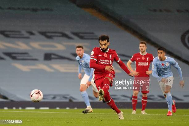 Liverpool's Egyptian midfielder Mohamed Salah shoots from the penalty spot to score the opening goal during the English Premier League football match...