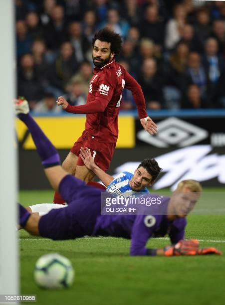 Liverpool's Egyptian midfielder Mohamed Salah shoots past Huddersfield Town's German defender Christopher Schindler and Huddersfield Town's Danish...