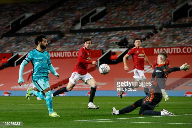 Liverpool's Egyptian midfielder Mohamed Salah shoots past Manchester United's English goalkeeper Dean Henderson to score the opening goal during the...