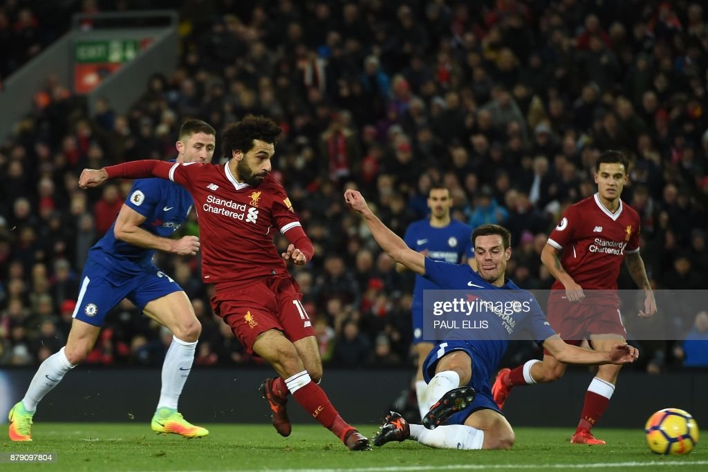 Liverpool's Egyptian midfielder Mohamed Salah (2nd L) shoots past the challenge of Chelsea's Spanish defender Cesar Azpilicueta (2nd R) to score the opening goal of the English Premier League football match between Liverpool and Chelsea at Anfield in Liverpool, north west England on November 25, 2017. / AFP PHOTO / Paul ELLIS / RESTRICTED TO EDITORIAL USE. No use with unauthorized audio, video, data, fixture lists, club/league logos or 'live' services. Online in-match use limited to 75 images, no video emulation. No use in betting, games or single club/league/player publications. /