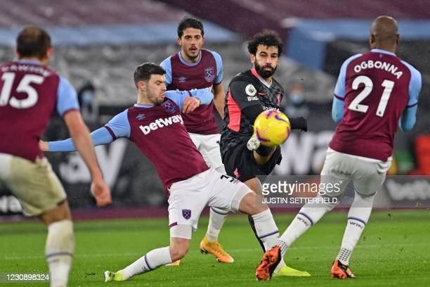 Liverpool's Egyptian midfielder Mohamed Salah shoots past West Ham United's English defender Aaron Cresswell to score the opening goal of the English...