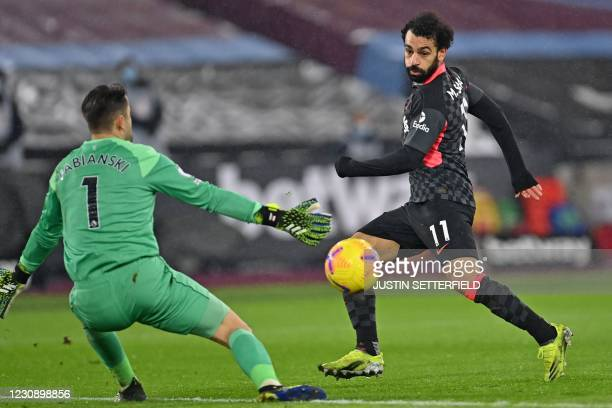 Liverpool's Egyptian midfielder Mohamed Salah shoots past West Ham United's Polish goalkeeper Lukasz Fabianski to score their second goal during the...