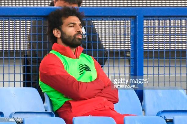 Liverpool's Egyptian midfielder Mohamed Salah sits on the bench during the English Premier League football match between Everton and Liverpool at...