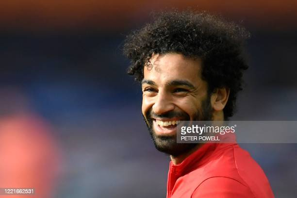 Liverpool's Egyptian midfielder Mohamed Salah smiles during the warm up for the English Premier League football match between Everton and Liverpool...