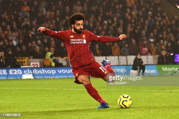 Liverpool's Egyptian midfielder Mohamed Salah takes a shot during the English Premier League football match between Wolverhampton Wanderers and...
