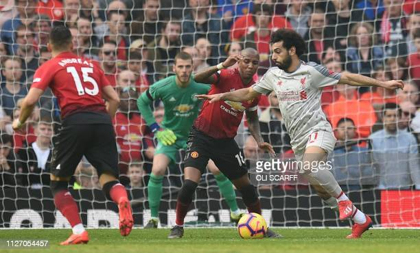 Liverpool's Egyptian midfielder Mohamed Salah takes on Manchester United's English midfielder Ashley Young as Manchester United's Spanish goalkeeper...
