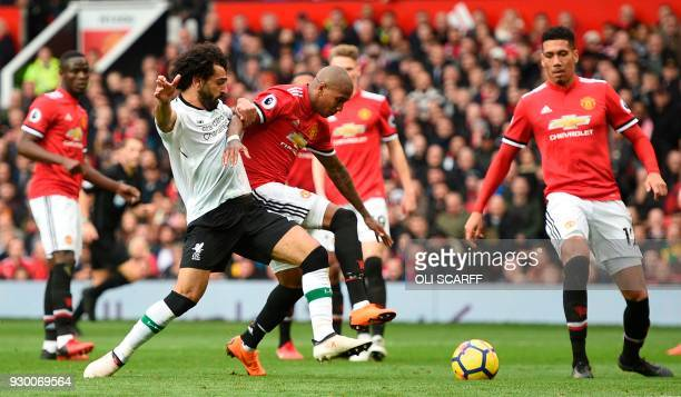Liverpool's Egyptian midfielder Mohamed Salah tangles with Manchester United's English midfielder Ashley Young during the English Premier League...
