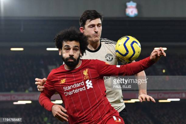 Liverpool's Egyptian midfielder Mohamed Salah tries to hold off Manchester United's English defender Harry Maguire during the English Premier League...