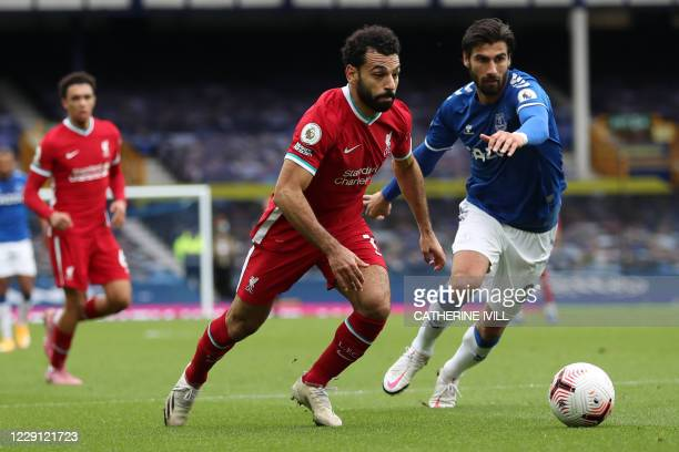 Liverpool's Egyptian midfielder Mohamed Salah vies with Everton's Portuguese midfielder André Gomes during the English Premier League football match...