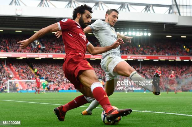 Liverpool's Egyptian midfielder Mohamed Salah vies with Manchester United's Italian defender Matteo Darmian during the English Premier League...