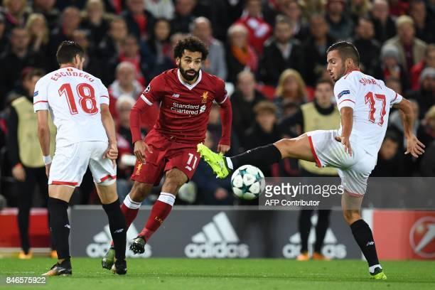 Liverpool's Egyptian midfielder Mohamed Salah vies with Sevilla's Spanish defender Sergio Escudero and Sevilla's Spanish midfielder Pablo Sarabia...