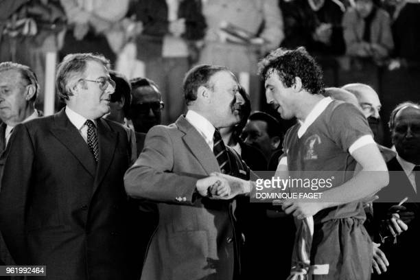 Liverpool's English defender Alan Kennedy is congratulated by an unidentified man as French Prime Minister Pierre Mauroy looks on after Liverpool won...