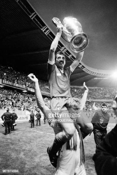 Liverpool's English defender Alan Kennedy sits on a teammates's shoulders as he raises the trophy while celebrating winning the European Cup final...