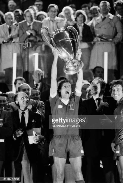 Liverpool's English defender and captain Phil Thompson raises the trophy as he celebrates winning the European Cup final football match between...