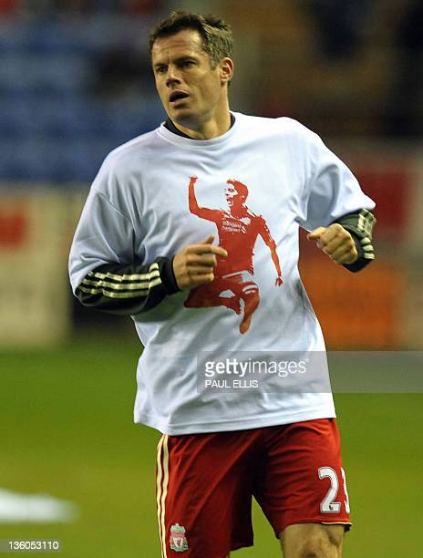 Liverpool's English defender Jamie Carragher warms up wearing a t-shirt supporting team-mate Luis Suarez before the English Premier League football...