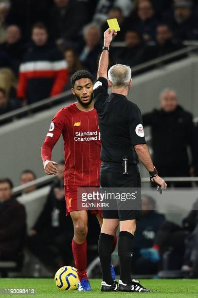 Liverpool's English defender Joe Gomez gets shown a yellow card by referee Martin Atkinson during the English Premier League football match between...