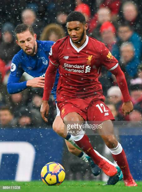 Liverpool's English defender Joe Gomez is chased by Everton's Icelandic midfielder Gylfi Sigurdsson during the English Premier League football match...