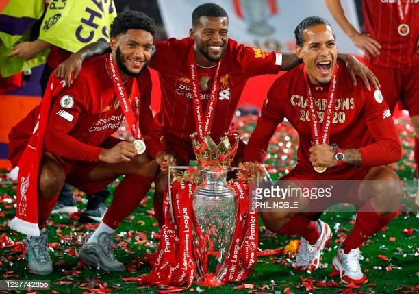 Liverpool's English defender Joe Gomez, Liverpool's Dutch midfielder Georginio Wijnaldum and Liverpool's Dutch defender Virgil van Dijk pose with the...
