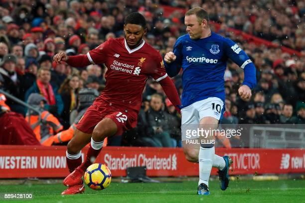 Liverpool's English defender Joe Gomez takes on Everton's English striker Wayne Rooney during the English Premier League football match between...