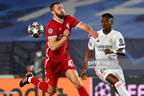 Liverpool's English defender Nathaniel Phillips challenges Real Madrid's Brazilian forward Vinicius Junior during the UEFA Champions League first leg...
