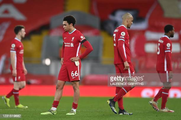 Liverpool's English defender Trent Alexander-Arnold and Liverpool's Brazilian midfielder Fabinho react at the final whistle during the English...