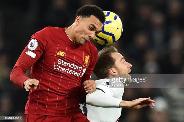 Liverpool's English defender Trent AlexanderArnold beats Tottenham Hotspur's Danish midfielder Christian Eriksen in the air during the English...
