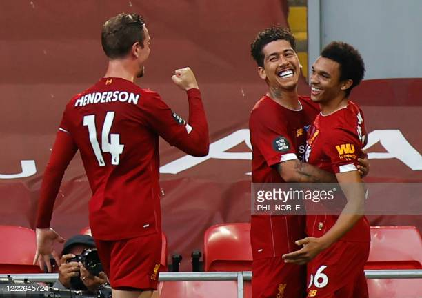 Liverpool's English defender Trent AlexanderArnold celebrates scoring the opening goal with Liverpool's Brazilian midfielder Roberto Firmino and...