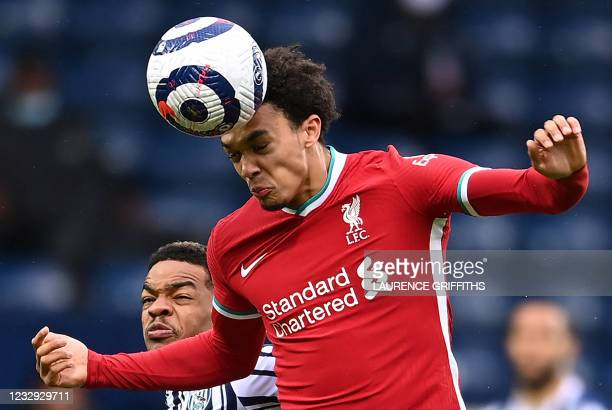 Liverpool's English defender Trent Alexander-Arnold heads the ball under pressure from West Bromwich Albion's DR Congo-born English midfielder Grady...