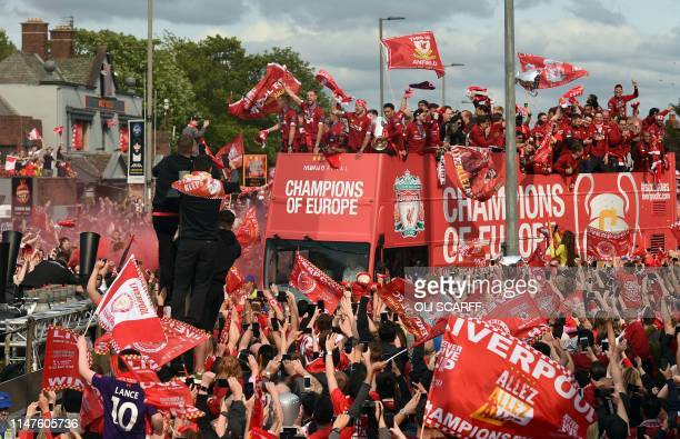 Liverpool's English defender Trent AlexanderArnold holds the European Champion Clubs' Cup trophy during an opentop bus parade for fans around...