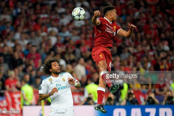 Liverpool's English defender Trent AlexanderArnold jumps for the ball next to Real Madrid's Brazilian defender Marcelo during the UEFA Champions...