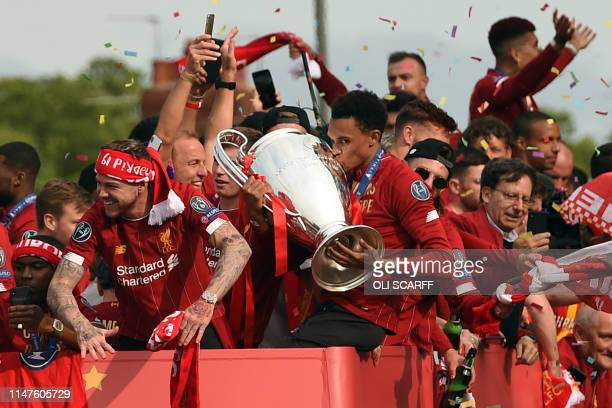 Liverpool's English defender Trent Alexander-Arnold kisses the European Champion Clubs' Cup trophy during an open-top bus parade around Liverpool,...