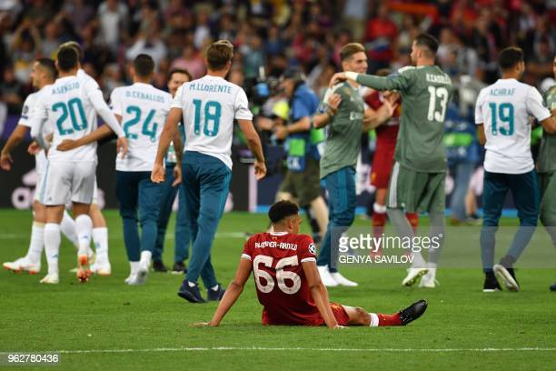 Liverpool's English defender Trent AlexanderArnold reacts as Real Madrid's players celebrate after winning the UEFA Champions League final football...