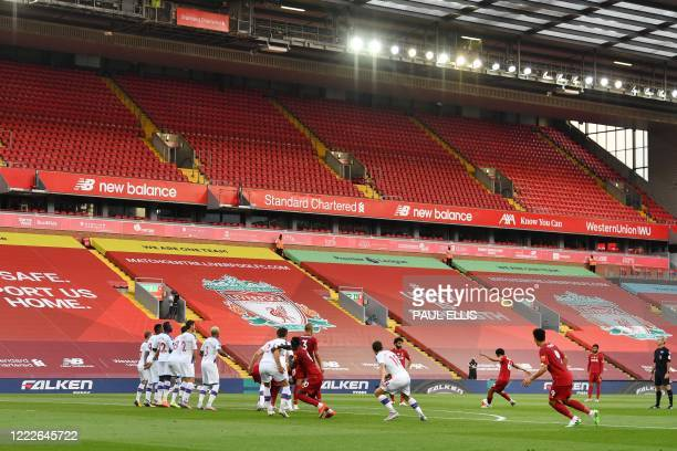 Liverpool's English defender Trent Alexander-Arnold scores the opening goal from a free kick, in front of empty seats and stands during the English...