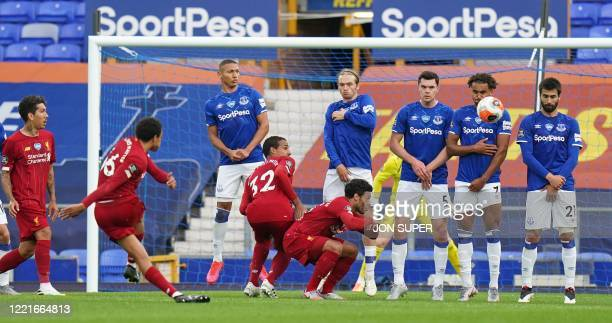 Liverpool's English defender Trent AlexanderArnold shoots at goal from a free kick during the English Premier League football match between Everton...