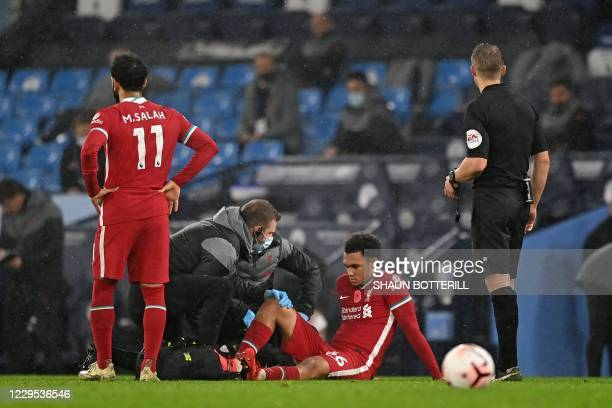 Liverpool's English defender Trent Alexander-Arnold sits on the ground after picking up an injury during the English Premier League football match...