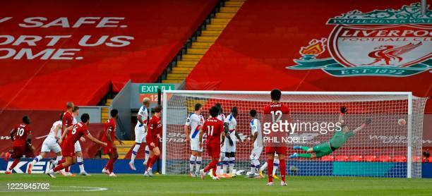 Liverpool's English defender Trent AlexanderArnold watches his shot as he scores the opening goal from a freekick during the English Premier League...