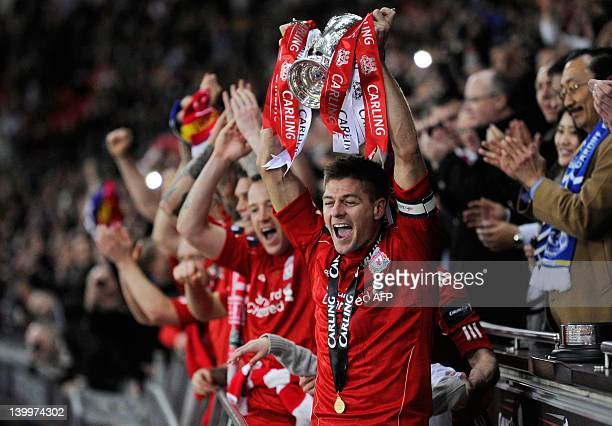 Liverpool's English footballer Steven Gerrard lifts the trophy after beating Cardiff City in a penalty shoot out in the League Cup Final at Wembley...