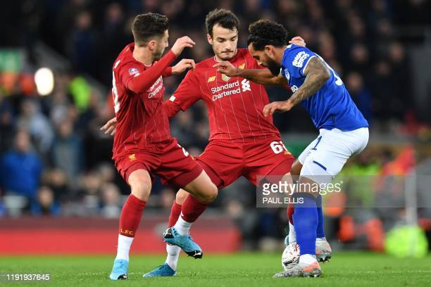 Liverpool's English midfielder Adam Lallana and Liverpool's Spanish midfielder Pedro Chirivella tackle Everton's English striker Theo Walcott during...