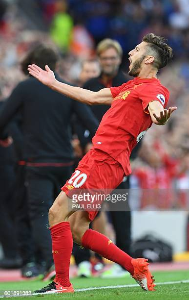 Liverpool's English midfielder Adam Lallana celebrates after scoring their third goal during the English Premier League football match between...