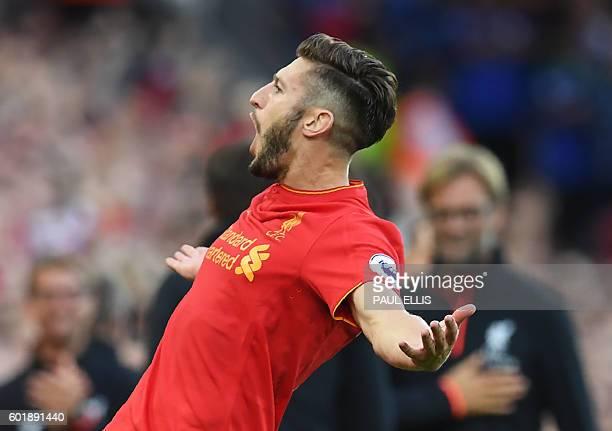 Liverpool's English midfielder Adam Lallana celebrates after scoring their third goal during the English Premier League football match between...